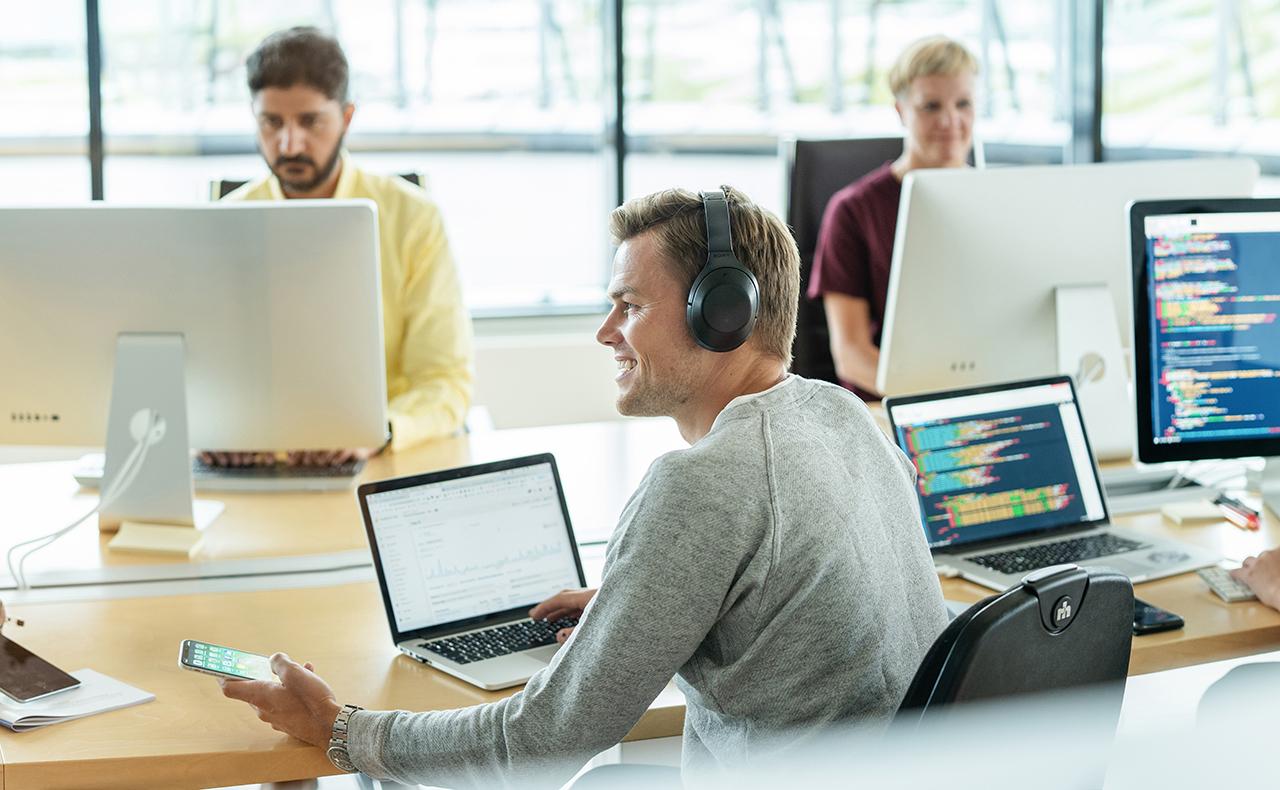 Man med hörlurar vid dator