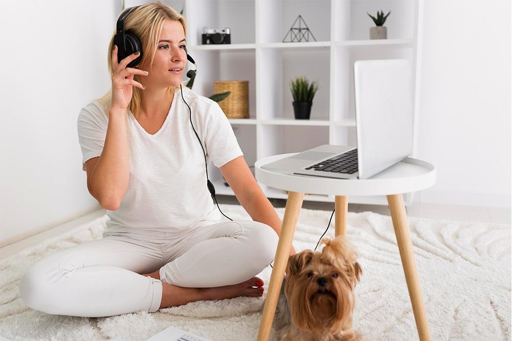 Kvinna hemmakontor headset med hund.