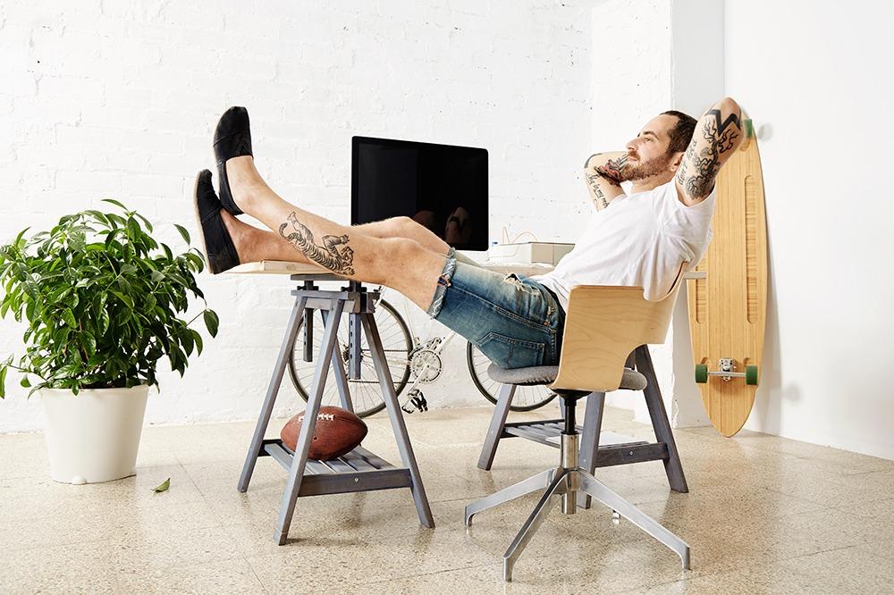 Vilar i kontorsstolen med skateboard och cykel längs väggen.