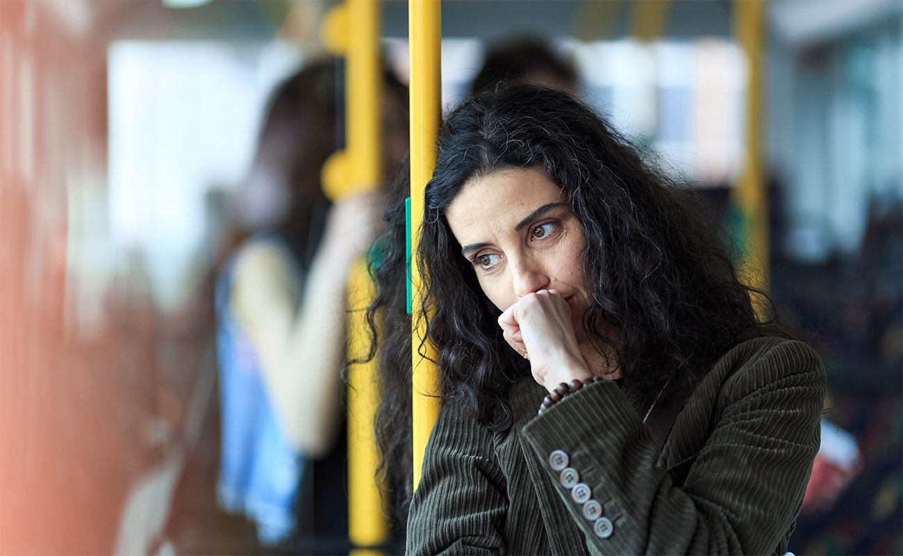 Kvinna står på buss och funderar på om hon ska lämna in ansökan om uppsägning
