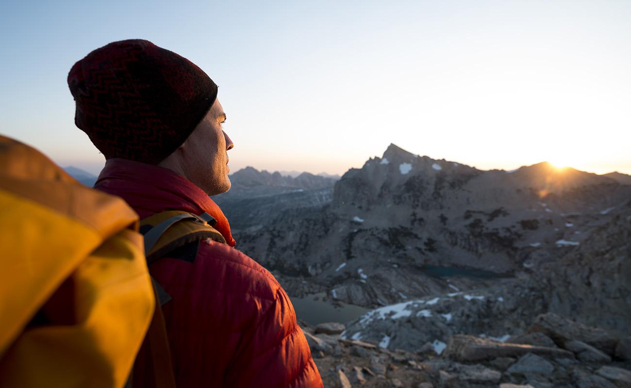 man tittar bort mot solnedgång bland bergen
